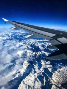 Plane wing over snowy mountains